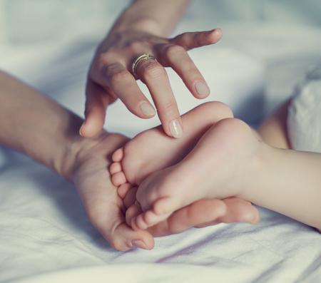 massage enfant: les pieds du bébé dans les mains de sa mère, dans le lit à la maison Banque d'images