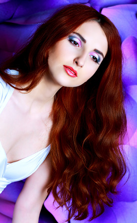 beautiful young model with long red hair and creative colorful makeup, studio photo
