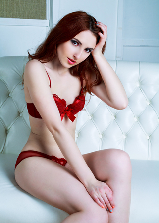 sexy young woman wearing red lingerie on the sofa at home