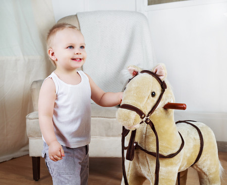 passtime: happy boy playing with a toy horse at home