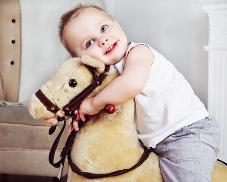 passtime: happy one and a half year old boy playing with a toy horse at home
