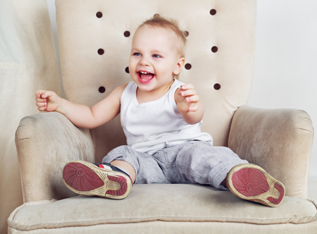 passtime: happy one and a half year old boy sitting in the chair at home