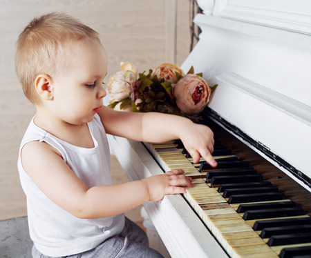 old piano: one year old baby boy playing an old piano Stock Photo