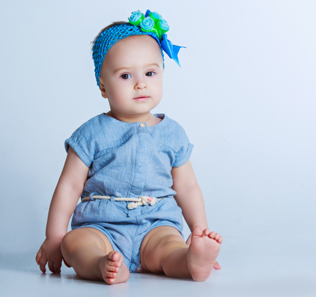 1 year old: beautiful one year old baby against blue studio background Stock Photo