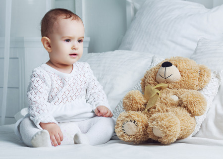 1 year old: one year old baby in bed at home with a toy Stock Photo