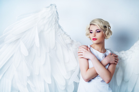 beautiful young model wearing a white dress with angel wings in the studio