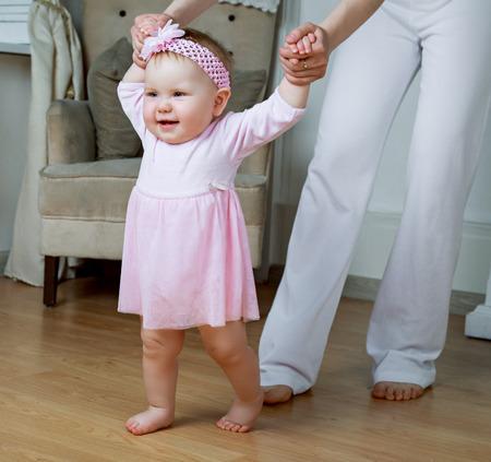 junge Mutter mit ihrem Baby Unterricht zu Hause zu Fuß