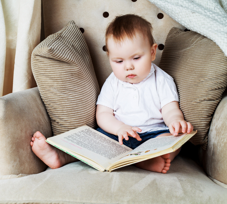 Prodigy: adorable baby reading a book in the chair at home