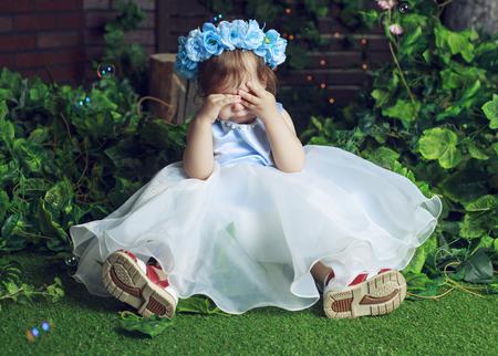 Huilende baby dragen van een bloem kroon in het bos Stockfoto - 56088418