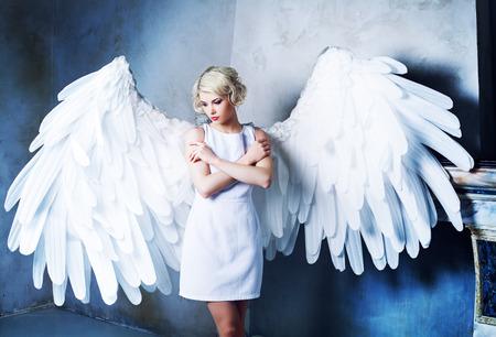 Piękna młoda modelka ubrana w białą suknię z anielskimi skrzydłami w studiu