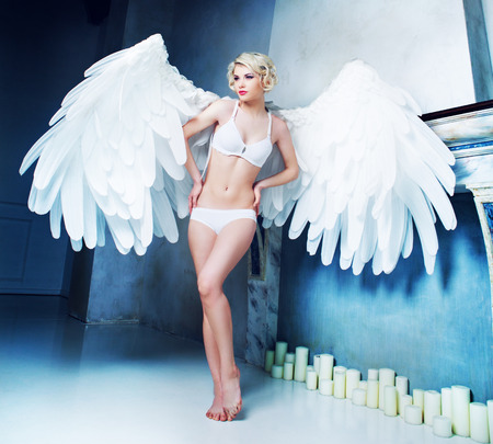 angel alone: beautiful young model wearing white underwear with angel wings in the studio