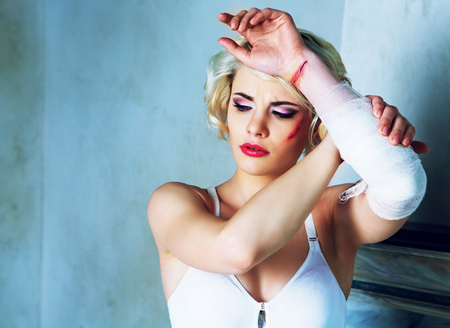 scar: beautiful young model wearing white underwear with wounds on her cheek and arm in the studio