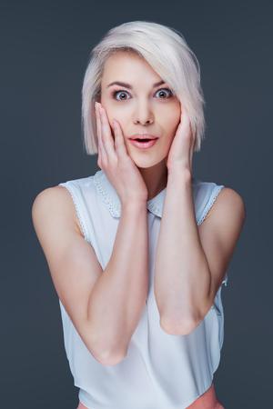 Mooie verrast vrouw geïsoleerd tegen grijze achtergrond