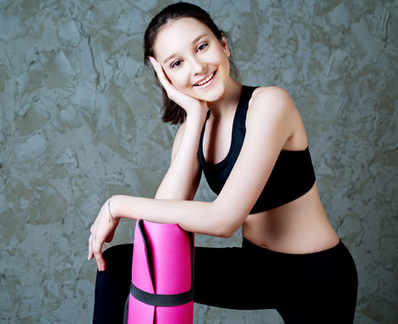 slim girl: beautiful smiling teenage girl wearing sports clothes with a yoga mat Stock Photo