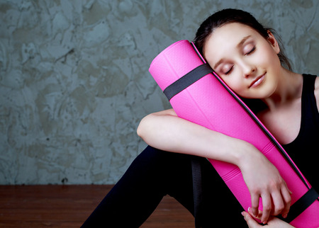 mat: beautiful smiling teenage girl wearing sports clothes with a yoga mat Stock Photo