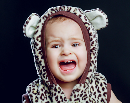 disobedient: unhappy crying one year old baby, isolated against black background Stock Photo