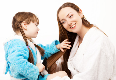 daughter brushing her mother's hair in bed at home photo