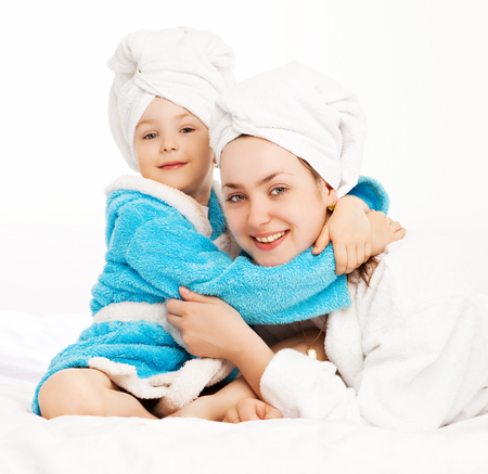 house robe: mother and daughetr wearing bathrobes in bed at home Stock Photo