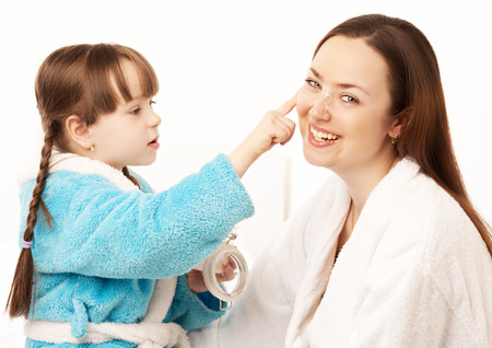 daughter applying cream on her mother's face in bed at home photo