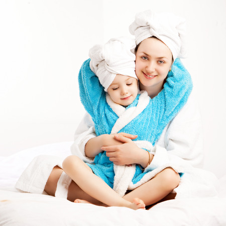 mother and daughetr wearing bathrobes in bed at home photo