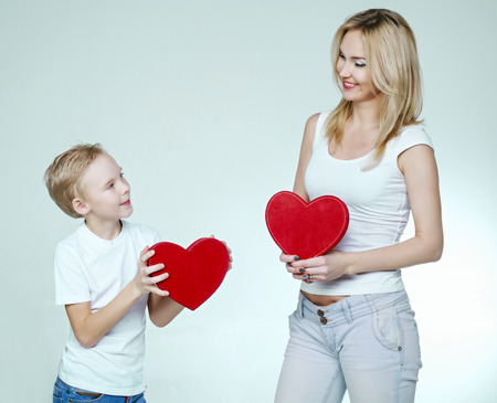 happy smiling mother and son with red heart-shaped gifts in their hands isolated against white background