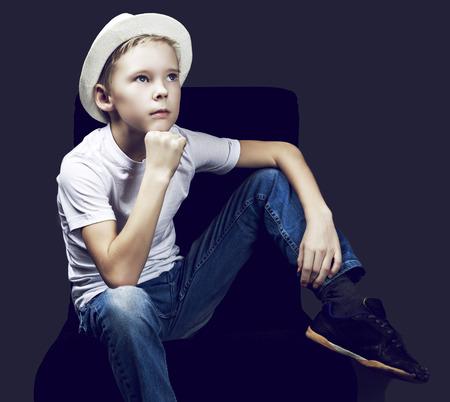 skinny: niño de nueve años de edad, llevaba un sombrero, contra el fondo oscuro Studioo