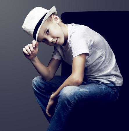skinny: elegantes nueve años de edad, muchacho con pantalones vaqueros y un sombrero, aislado contra el fondo oscuro del estudio