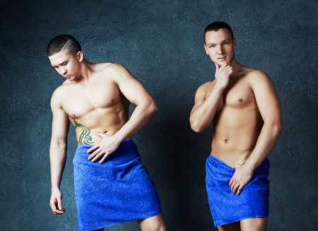 sex appeal: two attractive young men with towels on their hips after taking a shower, against studio background Stock Photo
