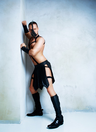 musculine: young strip dancer wearing a leather costume, in the studio