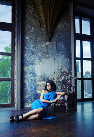 long depression: brunette woman wearing a blue dress in the room with old walls and furniture