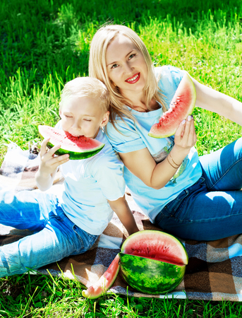 ten year old: happy young mother and her ten year old son eatign watermelon in the summer park Stock Photo