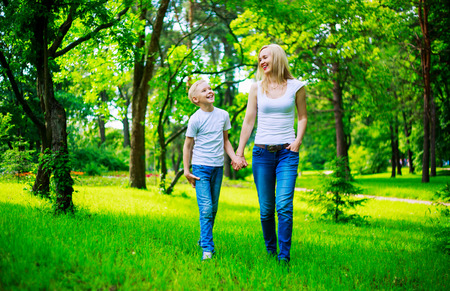 nine year old: happy young mother and her nine year old son in the summer park Stock Photo