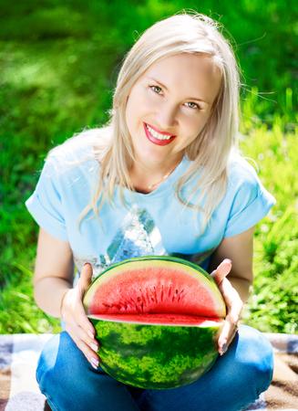 comiendo frutas: hermosa joven rubia con un melón de agua en el parque de verano