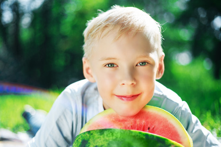 nine years old: happy nine years old boy eating watermelong in the park