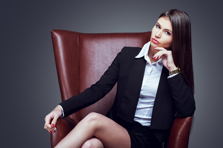 businesswoman suit: beautiful serious businesswoman with long hair in the char, isolated against grey studio background
