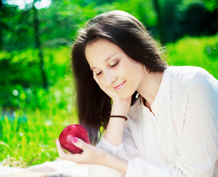 picnick: pretty teenage girl with an apple outdoor on a summer day Stock Photo
