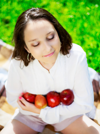 picnick: pretty teenage girl with apples outdoor on a summer day