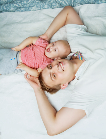 insides: happy young father with a baby  in bed at home