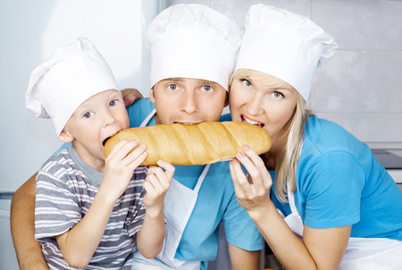 mother, father and son in the kitchen with bread photo