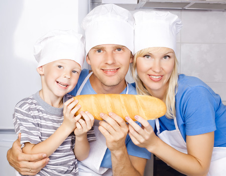 happy family: father, mother and son cooking in the kitchen at home and holding bread photo