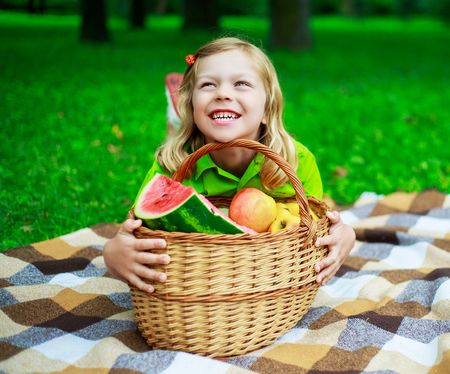 outsides: happy child with a fruit basket outdoor in the park Stock Photo