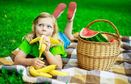 comiendo platano: niño feliz con los plátanos y una cesta de fruta en el parque al aire libre Foto de archivo