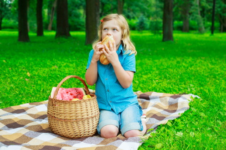 comiendo pan: niño con una cesta de fruta y pan al aire libre