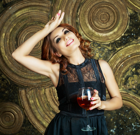 insides: happy young woman with a glass of wine in the studio