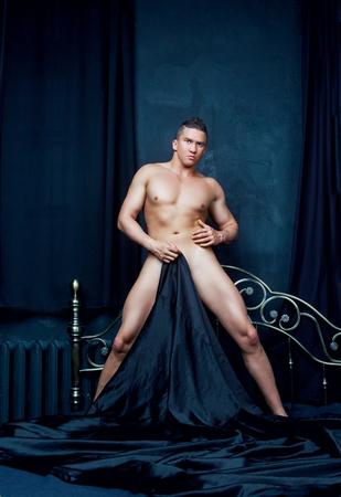 desnudo masculino: hombre desnudo atractivo en la cama con ropa de negro