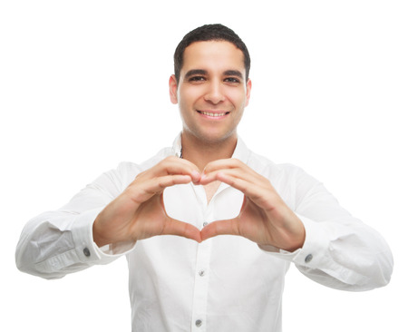 one man: happy smiling young man showing a sign of a heart with his fingers, isolated against white studio background