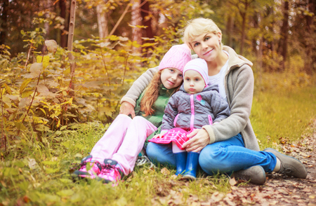 young pregnant mother with her two daughters in the autumn park