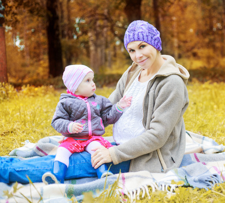 young pregnant mother with her daughter in the autumn park