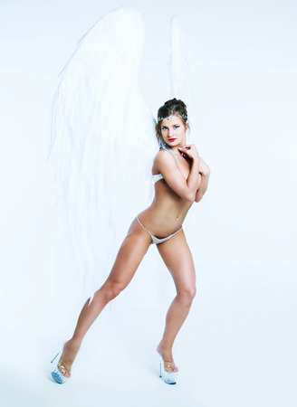 sexy women naked: beautiful striptease dancer wearing wings, against white studio background