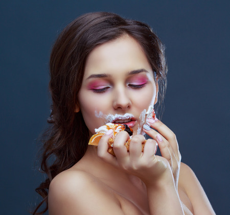 beautiful young model eating dessert in a very messy way, isolated
